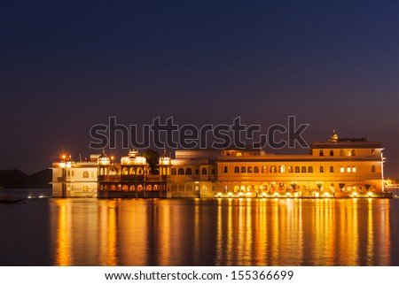 Romantic luxury India travel tourism - Lake Palace (Jag Niwas) complex on Lake Pichola in twilight, Udaipur, Rajasthan, India - stock photo