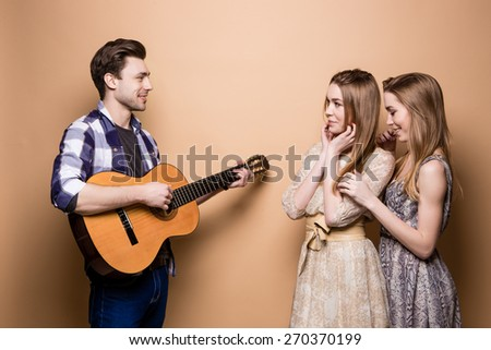 Romantic man playing guitar for two girls