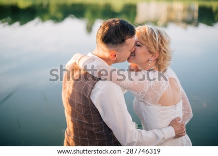 Romantic Married Couple. Bride and groom at wedding day spending some time with each other near beautiful lake - stock photo