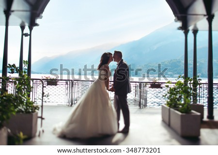 Romantic married couple kissing at port lake and mountains background - stock photo