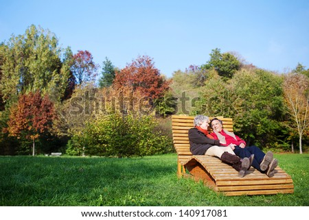Romantic mature couple sitting and talking outdoors - stock photo