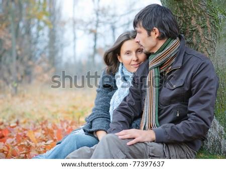 Romantic mature couple sitting in the autumn park. - stock photo