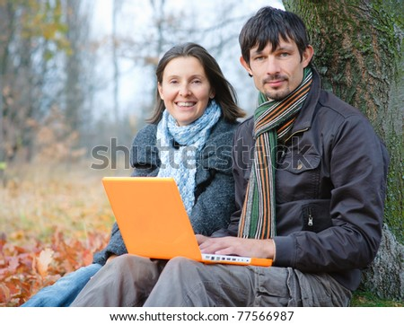Romantic mature couple sitting with laptop in the autumn park.