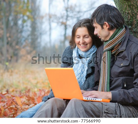 Romantic mature couple sitting with laptop in the autumn park. - stock photo