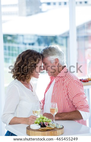 Romantic mature couple standing by table at restaurant