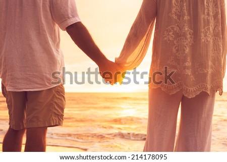 Romantic Mature Senior Couple Holding Hands Enjoying at Sunset on the Beach - stock photo