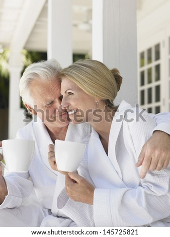Romantic middle aged couple in bathrobes with coffee cups sitting on verandah - stock photo