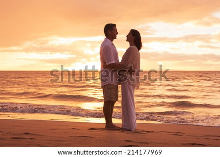 Romantic Middle Aged Couple in Love Embracing on the Beach at Sunset - stock photo