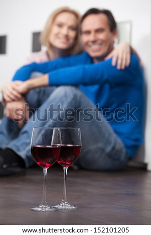 Romantic moments. Beautiful middle aged couple sitting on the floor and holding hands while two glasses of red wine standing on the foreground - stock photo