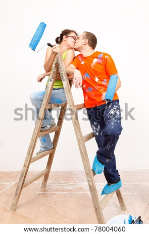 Romantic moments of a young pair during the wall painting