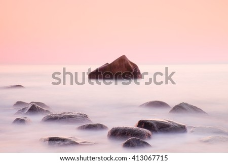 Romantic morning at sea. Big boulders sticking out from smooth wavy sea. Pink horizon with first hot sun rays. - stock photo