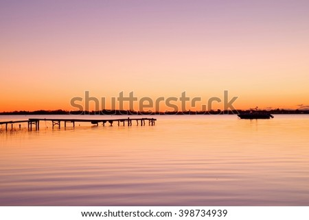 Romantic morning in harbor. Tourists pier construction above sea. Sunny clear blue sky, smooth water level, sporty boat. - stock photo