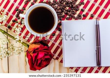 romantic mug of coffee and rose on striped napkin - stock photo
