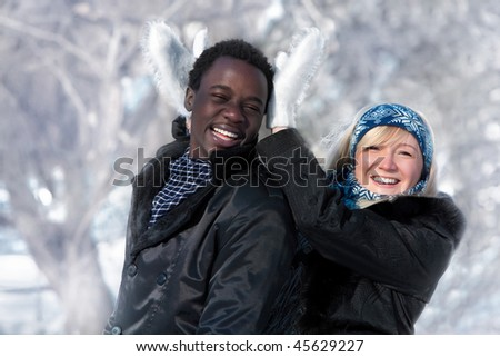Romantic multi-etnic couple is playing in the winter park - stock photo