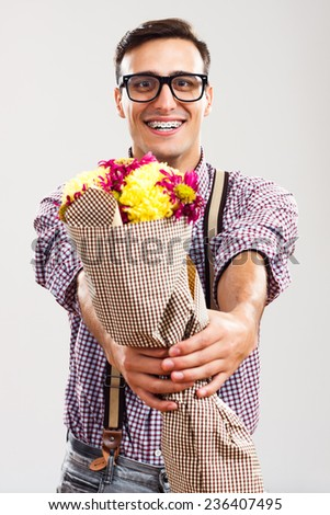 Romantic nerdy man is giving a bouquet of flowers to you.Flowers for you! - stock photo