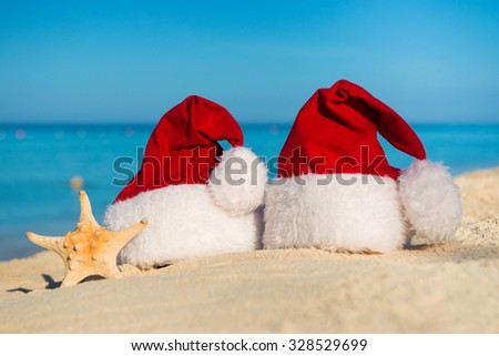 Romantic New Year at Sea. Christmas vacation. Santa hats on sandy beach - stock photo