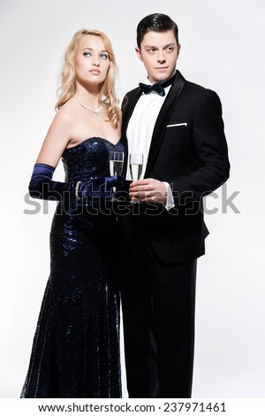 Romantic new year's eve fashion couple toasting with champagne. Wearing black dinner jacket and blue dress. Isolated against white. - stock photo