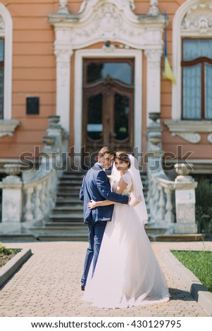 Romantic newly married couple charming bride and stylish groom posing in front of antique building entrance - stock photo