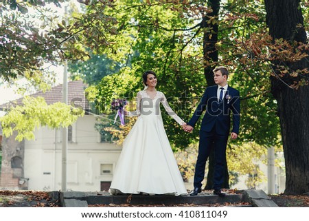 Romantic newlywed couple, bride & groom, posing in sunny park