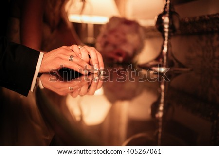 Romantic newlywed couple posing in hotel room, hands closeup