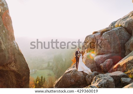 Romantic newlywed couple posing in sunset lights on majestic rocky mountain cliff with rural view as background