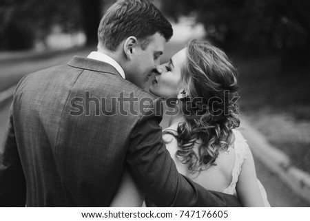 Romantic newlyweds couple hugging and kissing outdoors in summer park, stylish bride in wedding dress on a walk with handsome groom