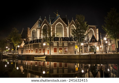 Romantic nocturnal view of Amsterdam: The Oude Church and canal in the Red District. Church and boats are reflected in the water  - stock photo