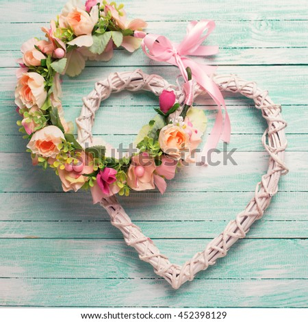 Romantic or wedding background. Flower wreath and decorative heart  on turquoise  wooden background. Selective focus. Square image.