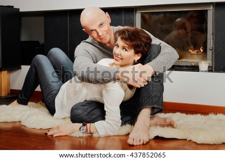 Romantic pair of brunette woman and bald headed man sitting on the fur carpet near a fireplace. Fire in the fireplace is burning.