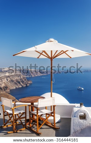Romantic patio with table and chairs for two on the Greek island of Santorini. - stock photo