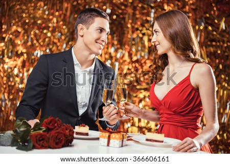 Romantic photo of beautiful couple on glitter gold background. Couple having date at Valentine's Day. Lovers having dinner. There are glasses with champagne, desserts, roses and gift on table - stock photo