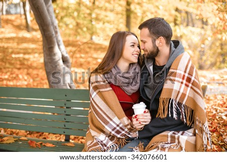 Romantic photo of cute couple outdoors in fall. Young man and woman sitting on bench with blanket, holding cup of coffee and smiling - stock photo