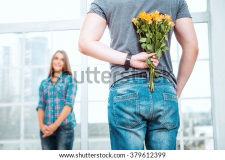 Romantic photo of happy young couple. Young man making surprise for his girlfriend. Man holding bouquet of yellow flowers behind his back - stock photo