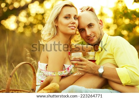 Romantic picnic concept. Portrait of young loving couple in trendy casual clothes drinking red wine and hugging each other. Basket with italian bread. Sunny autumn day. Copy-space. Outdoor shot - stock photo