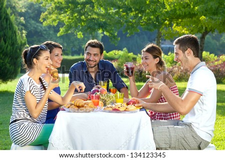 Romantic picnic. Group of five adult friends enjoying a healthy outdoor meal sitting together at a table in a lush green garden laughing and joking - stock photo