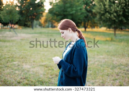 Romantic picture of a beautiful red-haired girl in the park on a sunny summer day - stock photo