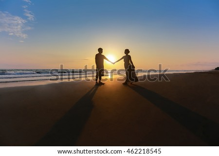 Romantic picture of Silhouettes young lover on the beach at sunset.
