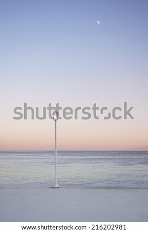Romantic pink and purple sunset coloring on a view of the Mediterranean Sea and a lamp post off the coast of Mykonos Greece. Moon is visible in the frame.  - stock photo
