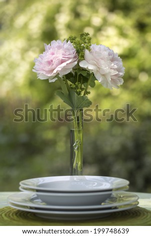 Romantic place setting with a tall elegant vase of fresh pink peonies served on a garden table against greenery for a Valentines or anniversary tryst - stock photo