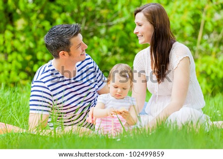 romantic playful couple outside with kids - stock photo