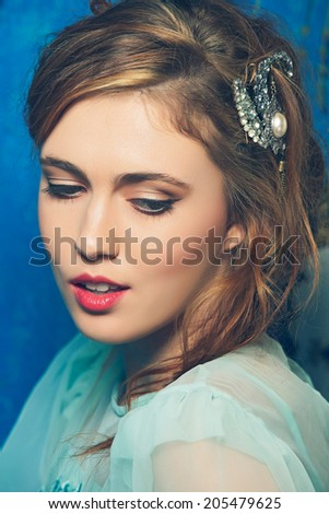 Romantic portrait of a young woman with braid hairstyle and luxury hair accessories on blue grunge texture background - stock photo