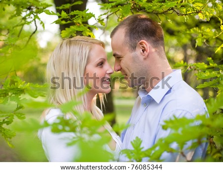 Romantic portrait of attractive young couple hiding in foliage. - stock photo