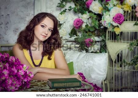 Romantic portrait of beautiful cheerful girl in room with flowers siting at the table - stock photo