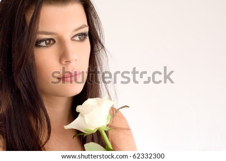 Romantic portrait of beautiful young brunette, holding a white a white rose, in front of white background.