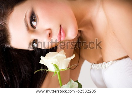 Romantic portrait of beautiful young brunette with white rose wearing a white dress.