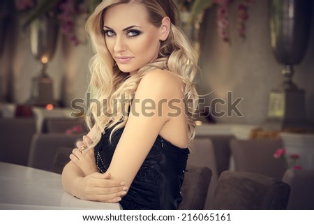 romantic portrait of cute beautiful blond with curly hair in luxury bar . loooking in camera smiling - stock photo