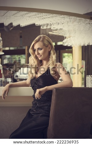 romantic portrait of elegand blond woman ,smiling on side sitting and waiting for someone in a luxury bar  - stock photo