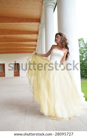 romantic portrait of the beautiful dancing princess in white-golden gown near pillars - stock photo