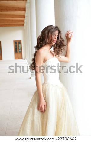 romantic portrait of the beautiful girl in white-golden gown near pillars - stock photo