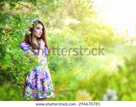 Romantic portrait of young beautiful girl standing at summer park and looking forward. - stock photo